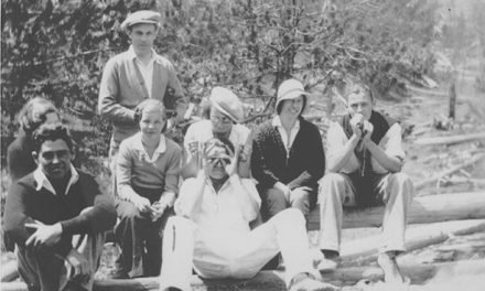 Eight people sitting on a log, 1930s