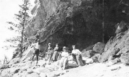 Hikers in front of a cave